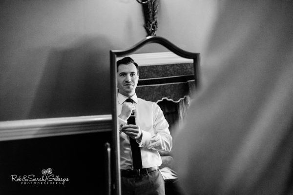 Groom fixes tie while getting ready for wedding at Coombe Abbey