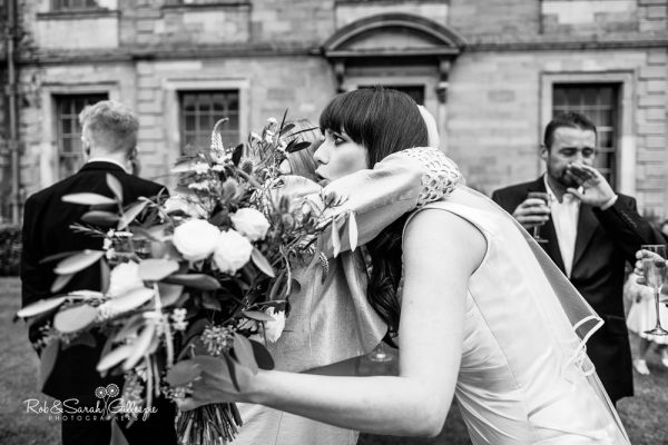 Bride hugged by wedding guest at Coombe Abbey