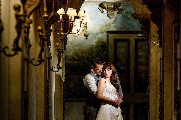 Bride and groom together in Coombe Abbey corridor with ornate decorations and lighting