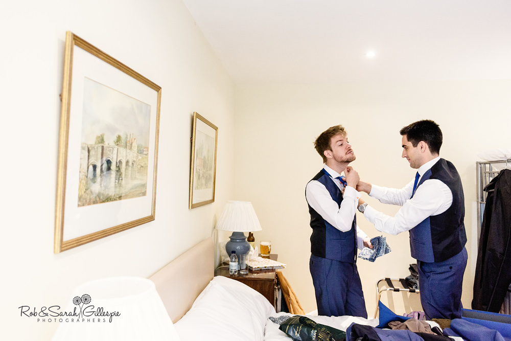 Groom has his tie fixed by friend at Delbury Hall Coach House