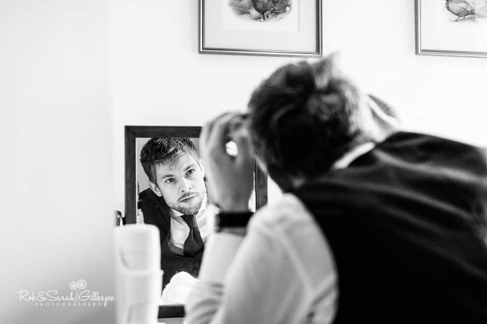 Groom checks his hair in mirror