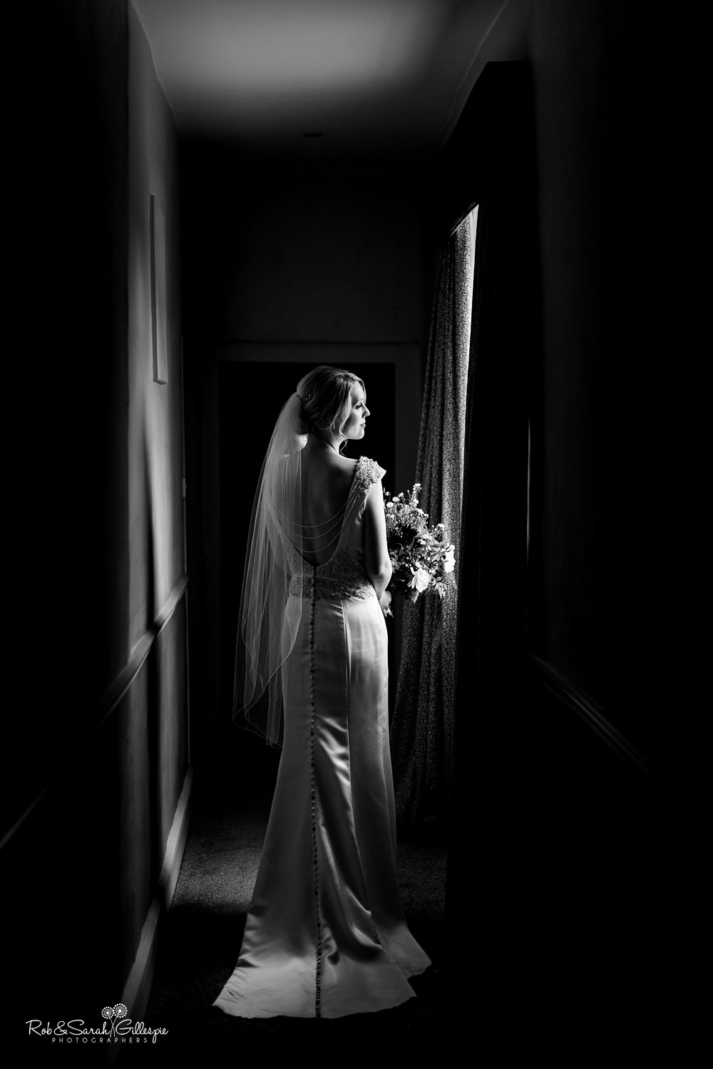Stunning black and white portrait of bride in beautiful window light at Delbury Hall Coach House