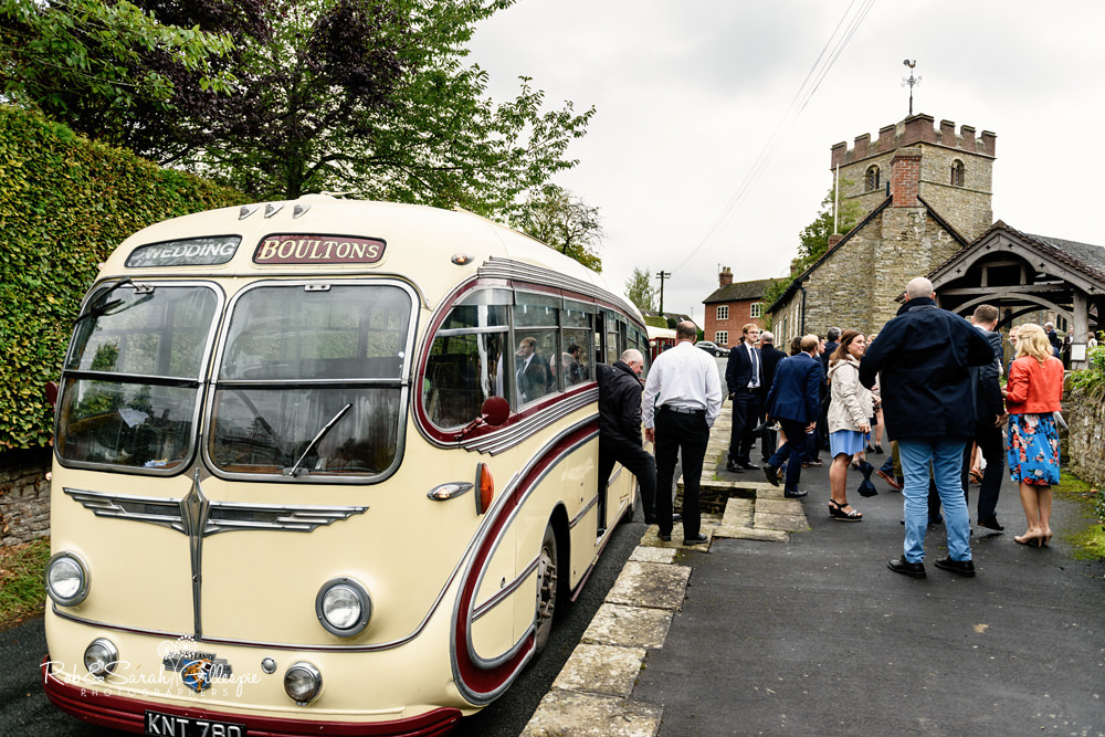 Wedding guests arrive on old coach for wedding at St Peter's church Diddlebury