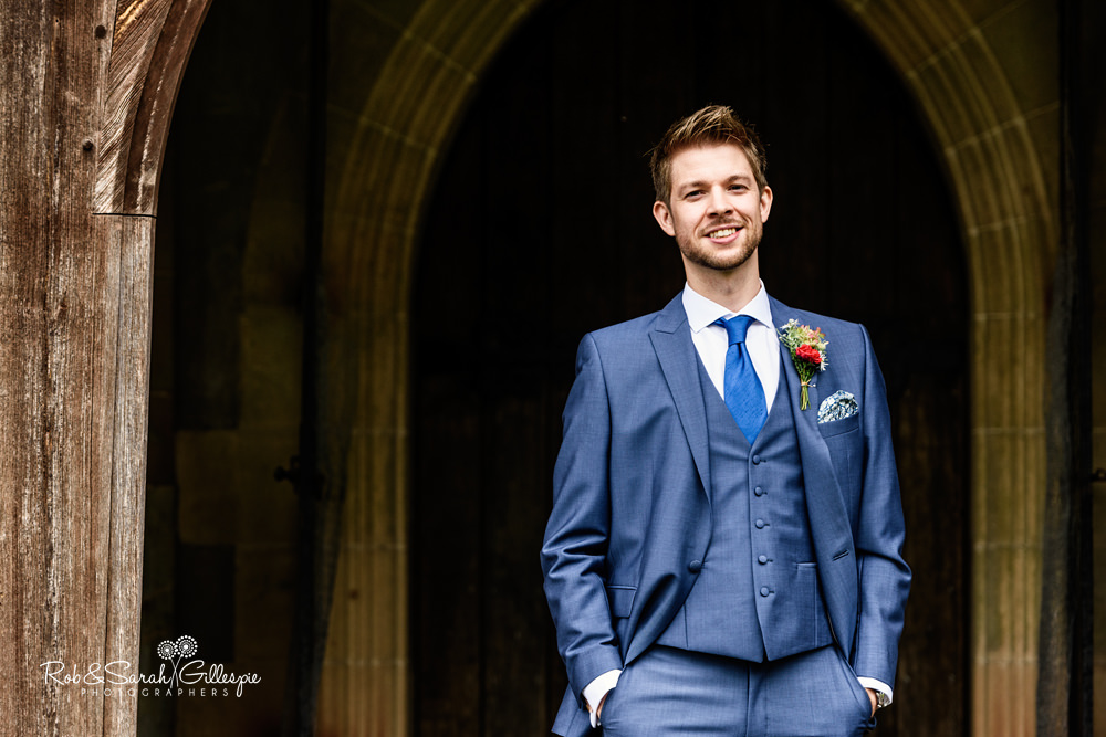 Portrait of groom in church doorway