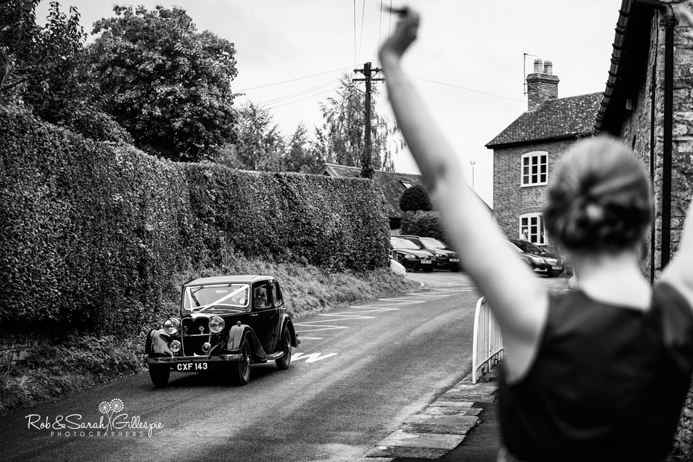 Bride arrives in old car at St Peter's Diddlebury as bridesmaid holds hands in the air