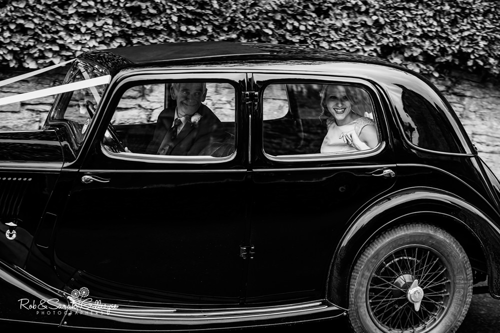 Bride smiling through window of old car as she arrives for wedding at St Peter's Diddlebury