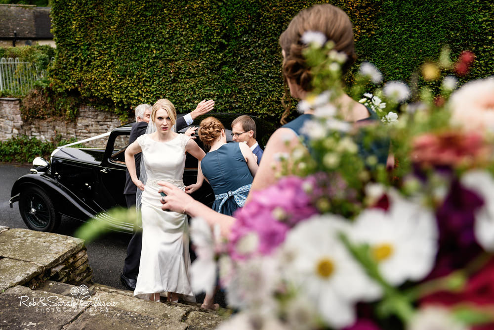 Bride gets out of car before wedding service at St Peter's Diddlebury
