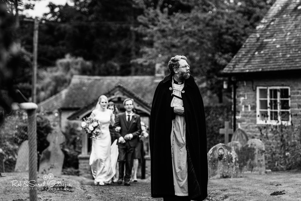 Vicar walks towards church as bride and father follow behind