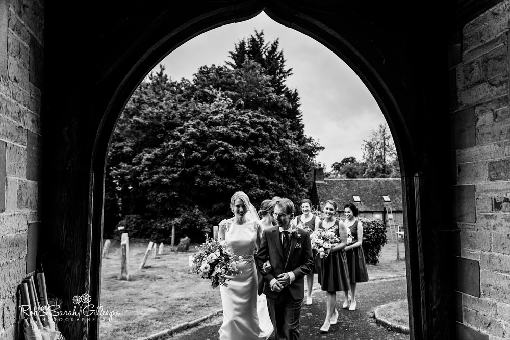Bride and bridesmaids walk towards St Peter's Diddlebury for wedding service