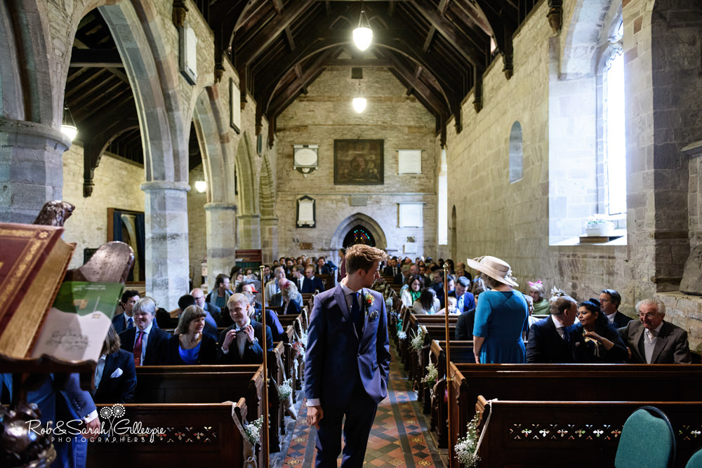 Groom waits for bride at St Peter's Church Diddlebury