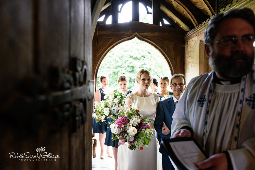 Bride and father wait to go inside church for wedding ceremony