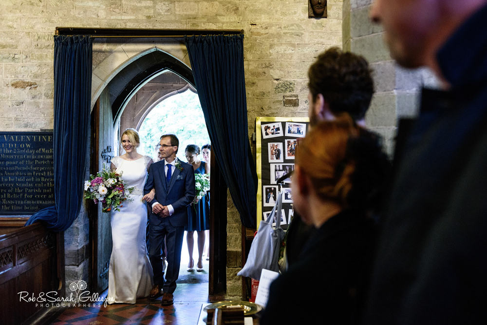 Bride and father enter St Peter's church Diddlebury for wedding ceremony