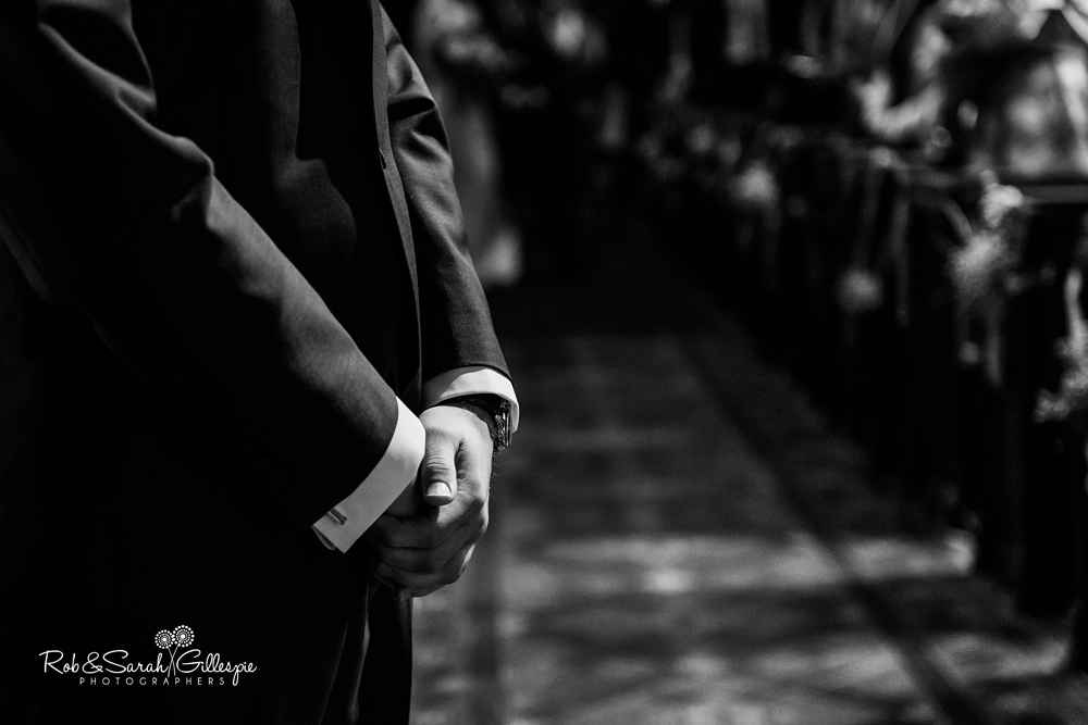 Close-up of groom's hands as he waits for his bride