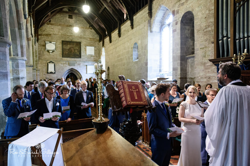 Bride and father walk up the aisle at St Peter's Church Diddlebury