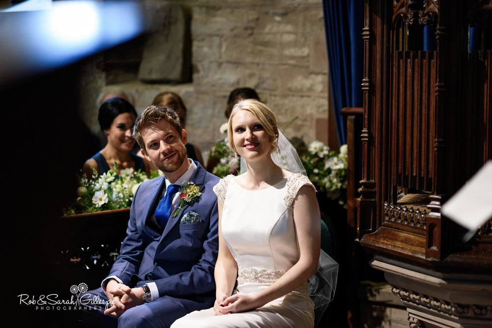 Bride and groom smiling at wedding guest during reading