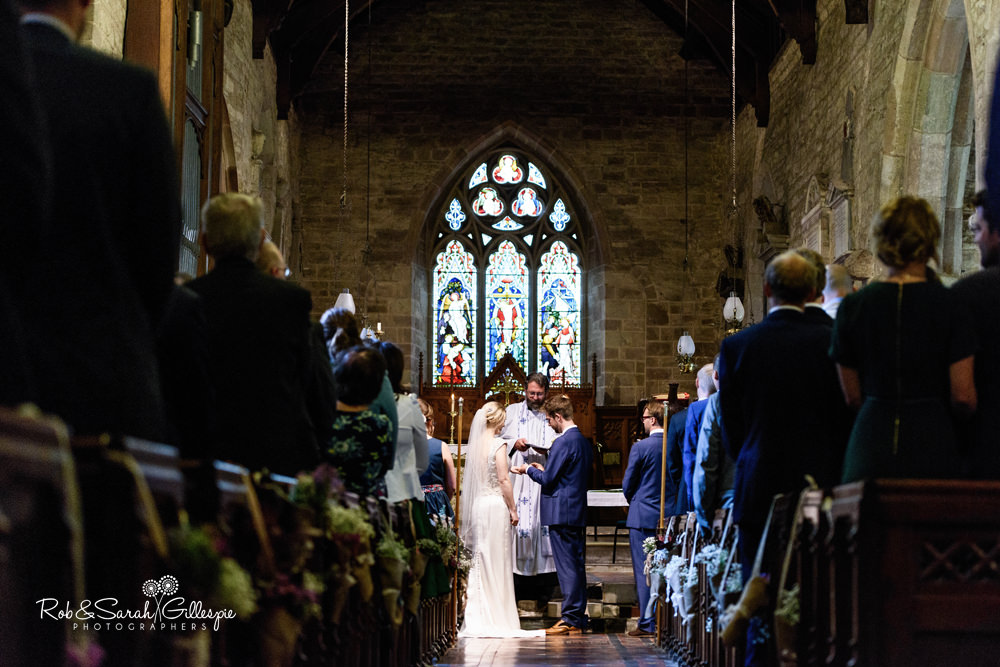 Bride and groom exchange vows and rings during wedding service at St Peter's Church Diddlebury