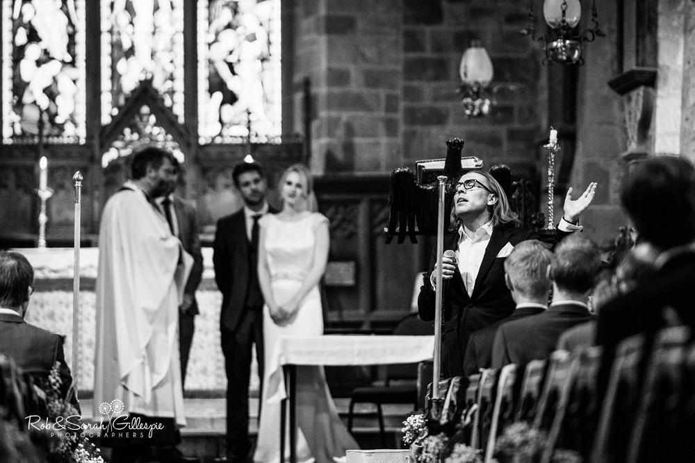 Wedding guest sings during church service as bride and groom look on
