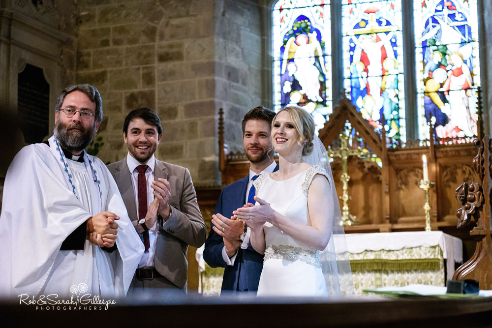 Wedding guests sings during church service as guests watch