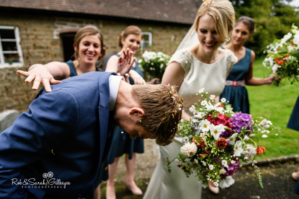 Bride and groom showered in confetti by wedding guests at St Peter's Church Diddlebury