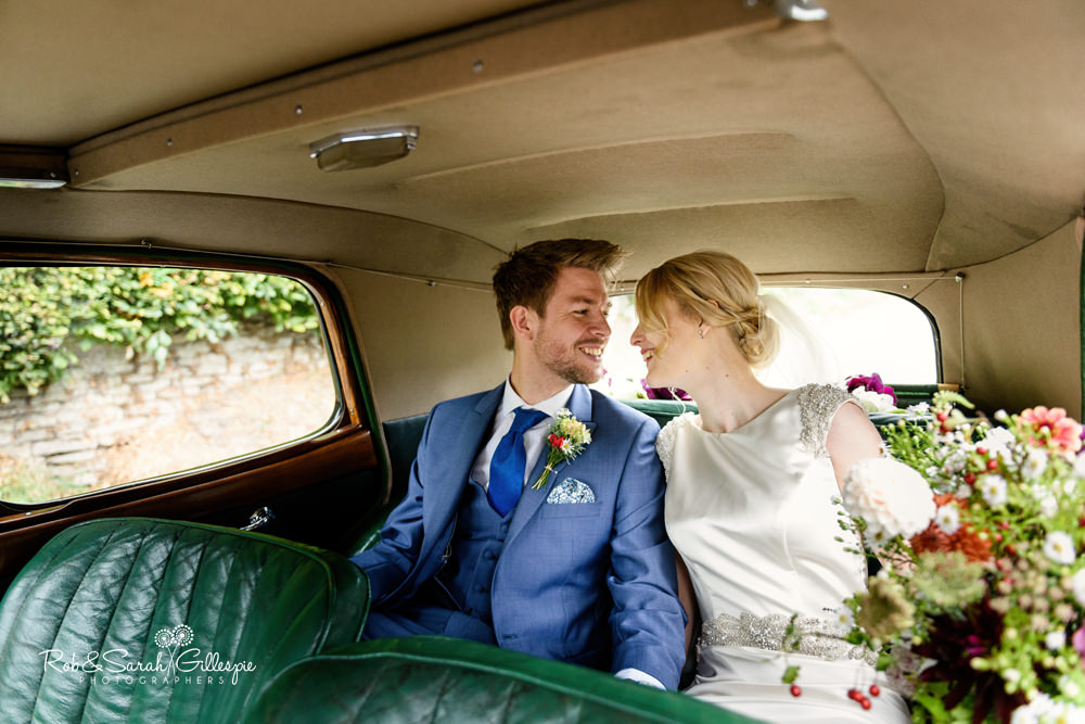 Bride and groom smiling at each other in old car as they leave church for wedding reception at Delbury Hall