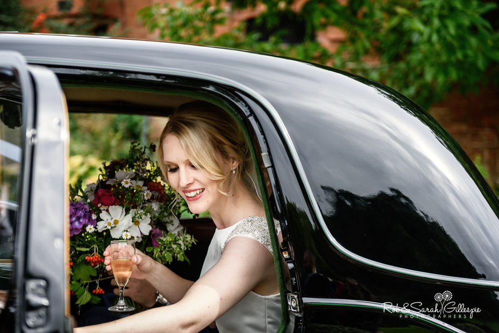 Bride smiling as she leaves wedding car at Delbury Hall