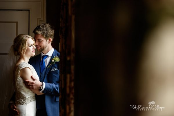 Bride and groom in window light at Delbury Hall