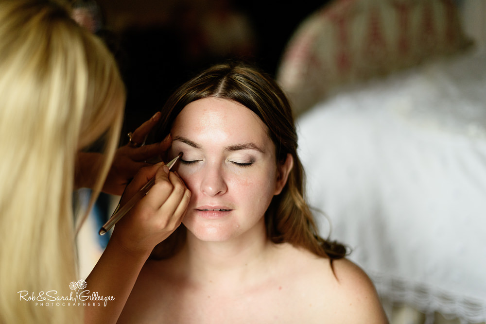 Bride having makeup applied at Eastnor Castle