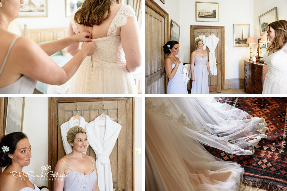 Bridesmaids helping bride with wedding dress at Eastnor Castle