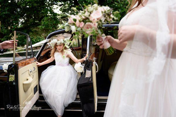 Flowergirl arrives at Malvern College wedding in old car