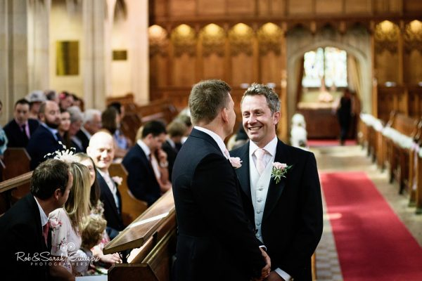 Groom chats with friend at Malvern College wedding