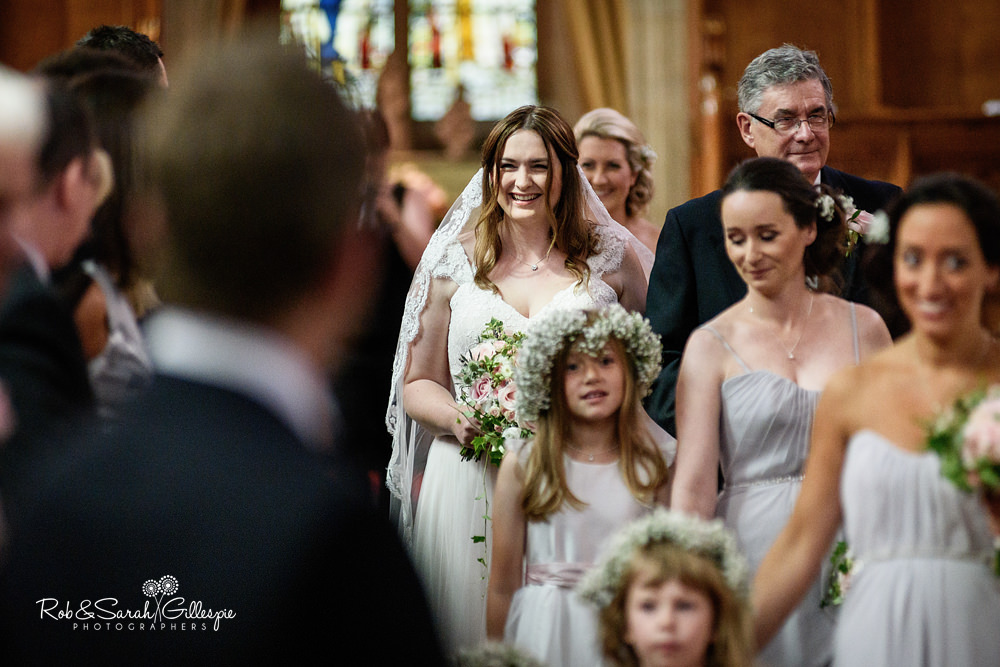 Groom smiling at bride as she walks up the aisle for wedding service in Malvern College chapel