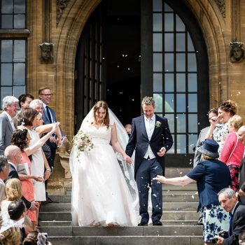 Bride and groom walk down steps as wedding guests throw confetti