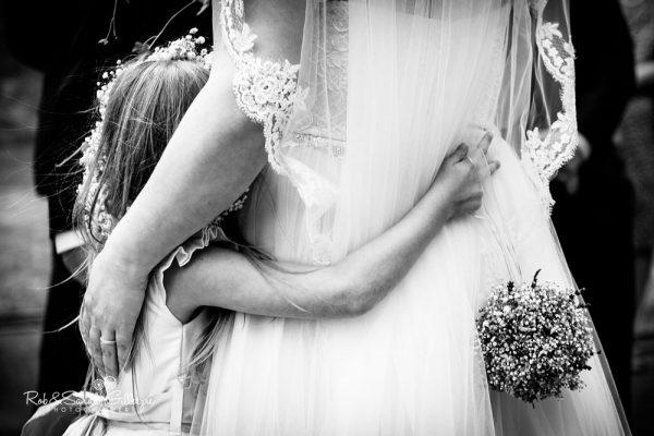 Flowergirl hjugs bride at Malvern College wedding