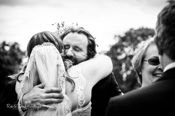 Wedding guest hugs bride at Malvern College