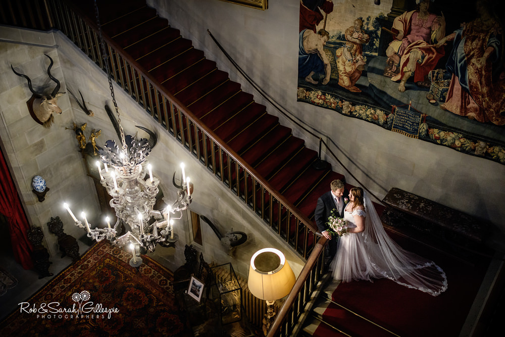 Bride and groom together looking out fo window at Eastnor Castle