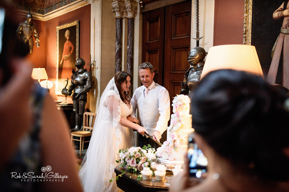 Bride and groom holding hands in doorway at Eastnor Castle