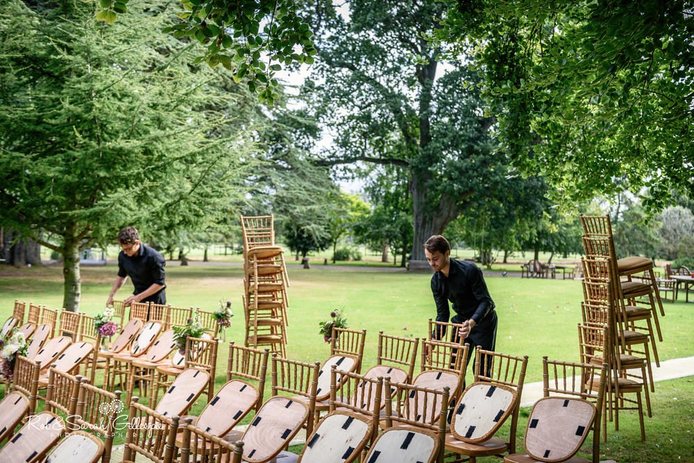 Chairs being arranged for outdoor wedding ceremony at Maunsel House in Somerset