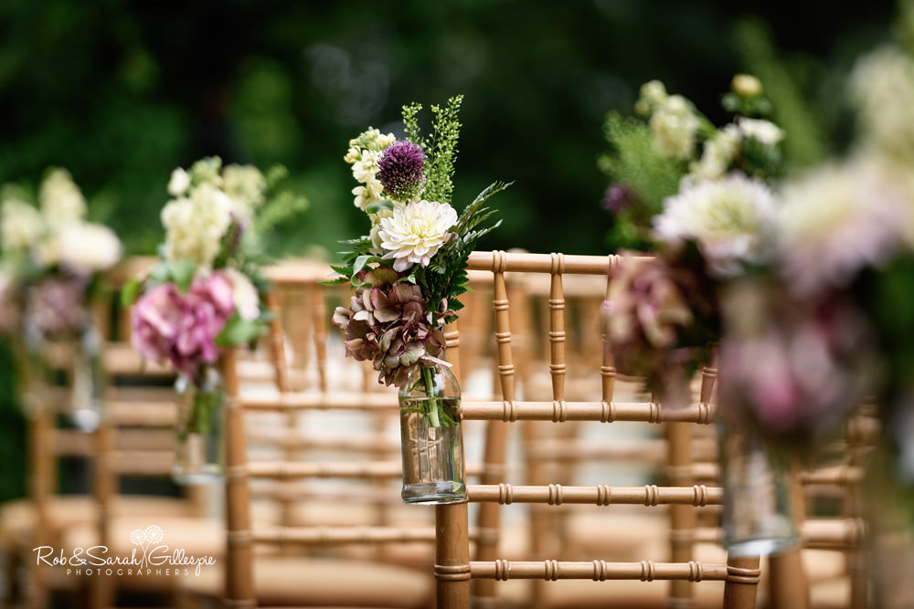 Flower arrangements tied to wooden chairs at Maunsel House outdoor wedding ceremony