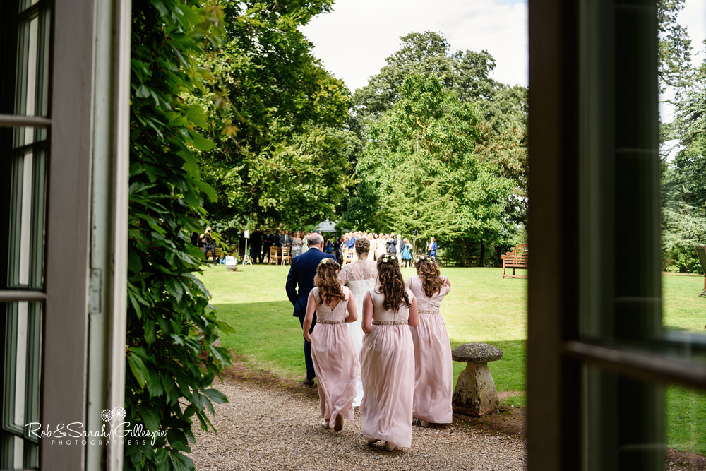 Bride and bridesmaids walk outside to wedding ceremony