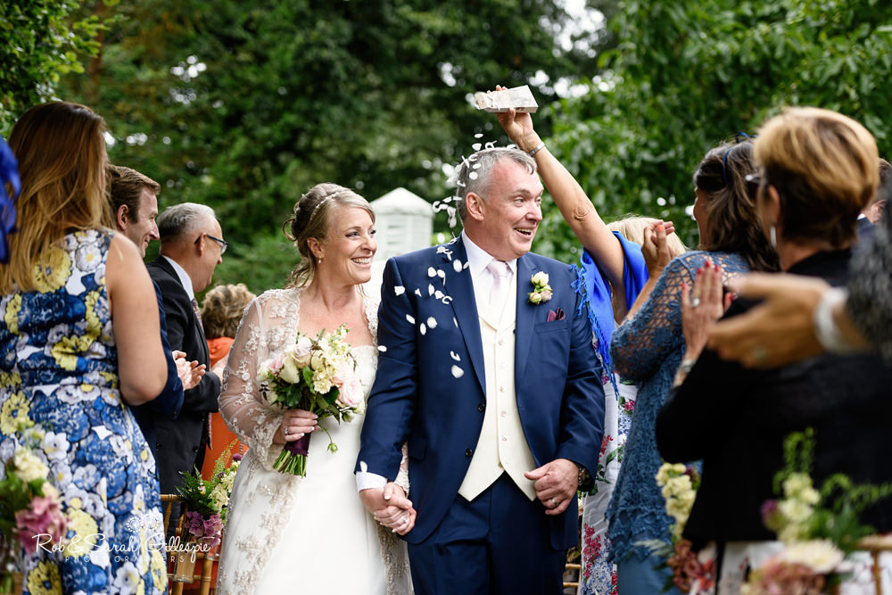 Bride and groom walk up the aisle with confetti at Maunsel House
