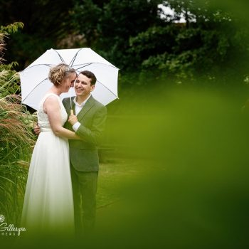 Bride and groom under umbrella at Monkey World in Dorset