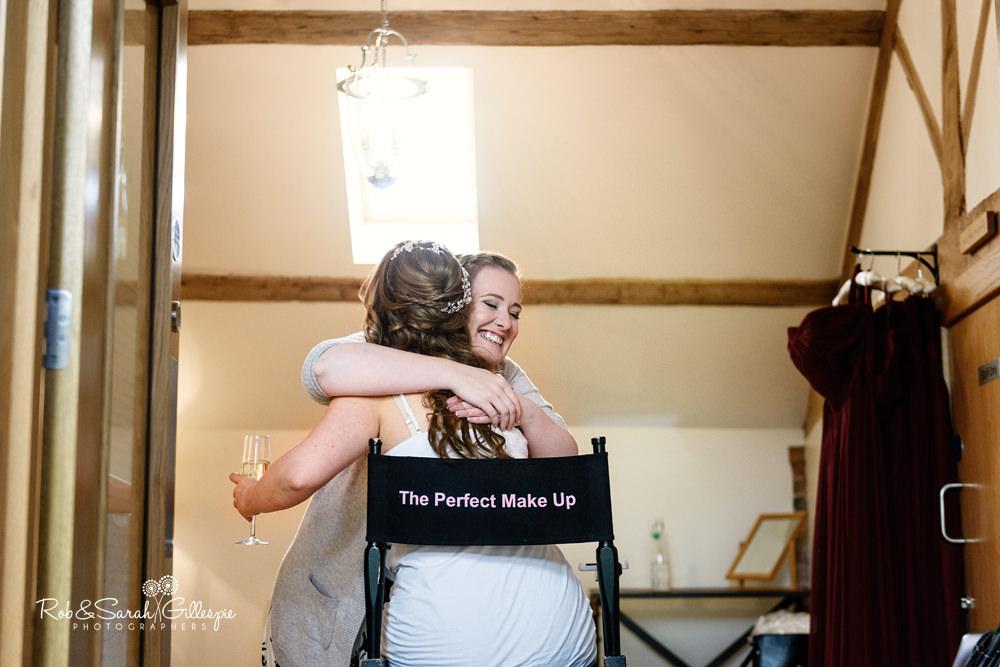 Bridesmaid hugs bride at Mythe Barn