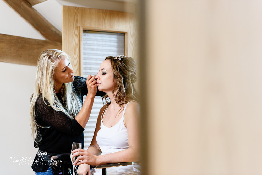 Bride has makeup applied in room at Mythe Barn