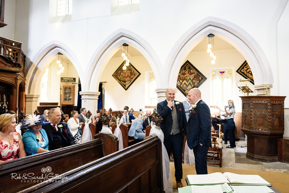 Groom and guests wait for bride at All Saints church Grendon