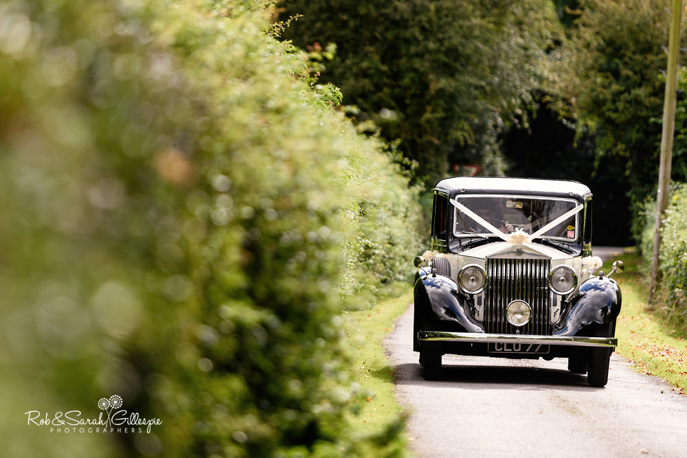 Wedding car arrives with bride at All Saints church Grendon