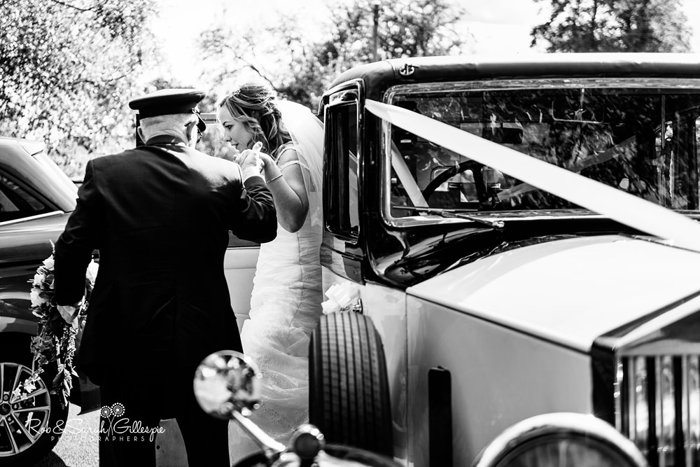 Bride steps out of car ready for wedding at All Saints church Grendon