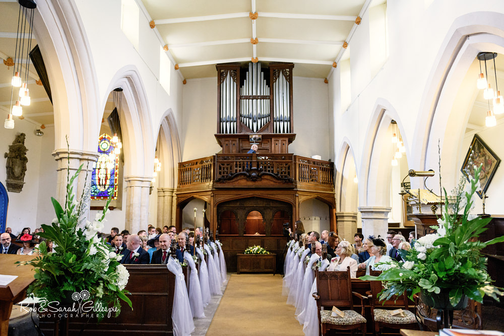 Wedding guests wait for bride to enter at All Saints church Grendon