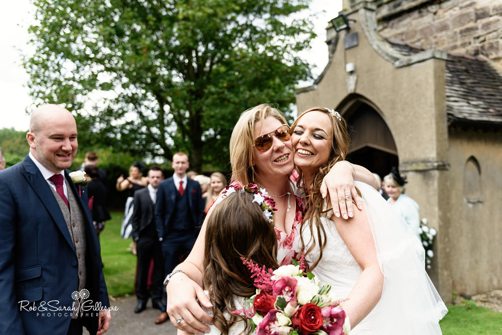 Wedding guests hug bride and groom at All Saints church Grendon