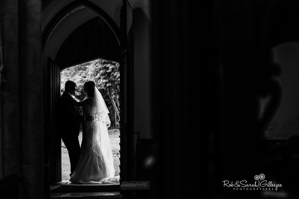 Bride and groom silhouetted in doorway at All Saints church Grendon
