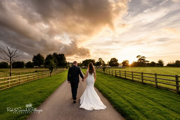 Bride and groom walk under dramatic sky at Mythe Barn
